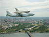 Space shuttle Discovery, mounted atop a NASA 747 Shuttle Carrier Aircraft (SCA), flies over the Washington skyline as seen from a NASA T-38 aircraft. Photo credit: NASA/Robert Markowitz