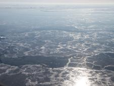 The sun reflects over thin sea ice and a few floating ice bergs near the Denmark Strait off of eastern Greenland.