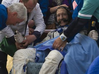 Expedition 30 Commander Dan Burbank smiles as he rests outside the Soyuz TMA-02M Capsule