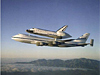 Space shuttle on top of an aircraft flying over mountains