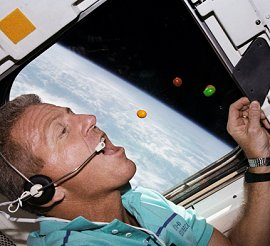 Astronaut Loren Shriver eats M and Ms onboard the space shuttle Atlantis.