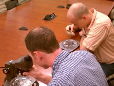 lsp employees view lunar sample disks through microscope