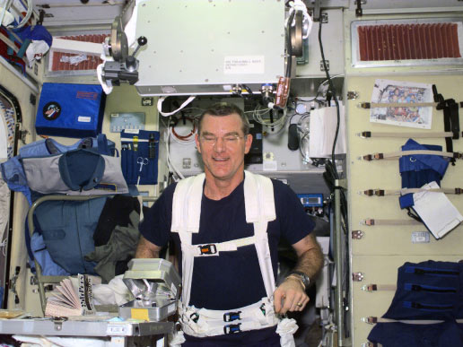Astronaut James S. Voss, Expedition Two flight engineer, wearing a safety harness, exercises on the Treadmill Vibration Isolation System  equipment in the Zvezda Service Module