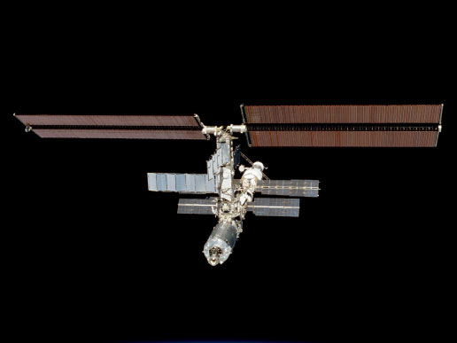 Backdropped against the blackness of space, the International Space Station (ISS) was photographed with a 35mm camera by one of the astronauts onboard Atlantis.
