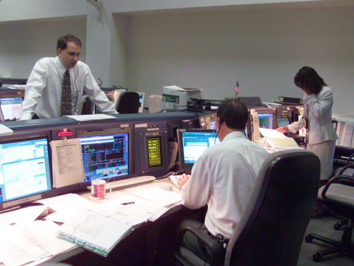 ISS Flight Director Mark Ferring (seated), Cargo Integration Officer Jim Ruhnke and astronaut Stephanie D. Wilson, ISS spacecraft communicator, are pictured at their consoles in the station flight control room in Houston's Mission Control Center during the STS-105 mission.