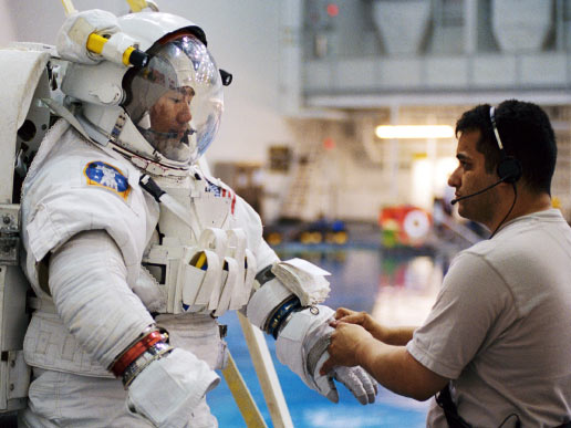 Astronaut Soichi Noguchi, STS-114 mission specialist, gets help with final touches on the training version of his Extravehicular Mobility Unit space suit prior to being submerged in the waters of the at the Johnson Space Center. Noguchi represents the Japan Aerospace Exploration Agency.