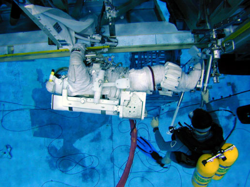 Astronaut Barbara R. Morgan, wearing a training version of the Extravehicular Mobility Unit spacesuit, participates in an underwater simulation of extravehicular activity at the Neutral Buoyancy Laboratory near Johnson Space Center. Divers assisted Morgan.