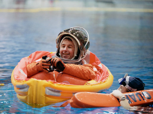 Astronaut Stephen K. Robinson, STS-114 mission specialist, assisted by divers, floats in a small life raft during an emergency egress training session in the Neutral Buoyancy Laboratory near the Johnson Space Center.
