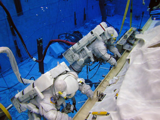 Astronauts Barbara R. Morgan (red stripes) and Janice E. Voss (solid white suit), wearing training versions of the Extravehicular Mobility Unit spacesuit, participate in an underwater simulation of extravehicular activity at the Neutral Buoyancy Laboratory near Johnson Space Center.