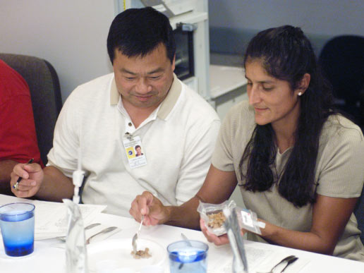 Astronauts Leroy Chiao (left) and Sunita L. Williams participate in food tasting in the Flight Projects Division Laboratory at the Johnson Space Center.