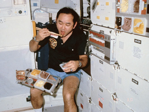 On Space Shuttle Discovery's middeck, astronaut Ellison S. Onizuka, mission specialist, uses a pair of chopsticks at mealtime. A sweet roll begins to float from the food tray in the microgravity environment of the Earth-orbiting Space Shuttle Discovery.