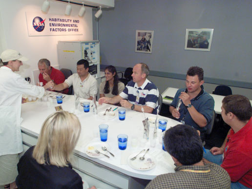 A group of astronauts and cosmonaut participate in food tasting in the Flight Projects Division Laboratory at the Johnson Space Center.