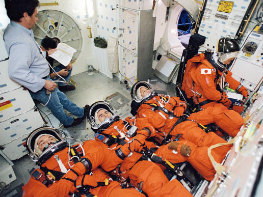 Cosmonauts Alexander Y. Kaleri (left), Expedition Seven flight engineer; Yuri I. Malenchenko, mission commander; astronauts Edward T. Lu, flight engineer; and Soichi Noguchi, STS-114 mission specialist; participate in mission training in one of the full-scale trainers in the Space Vehicle Mockup Facility at the Johnson Space Center.