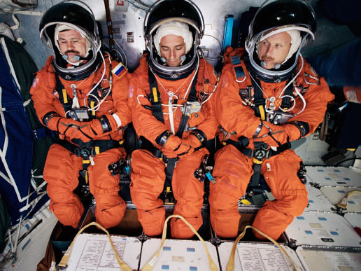 Cosmonaut Nikolai M. Budarin representing Rosaviakosmos, astronauts Donald R. Pettit and Kenneth D. Bowersox, wearing training versions of the shuttle launch and entry suit, participate in a training session in the Space Vehicle Mockup Facility at Johnson Space Center.