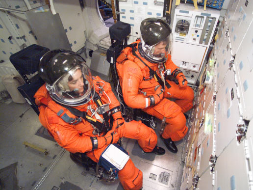 Astronauts Heidemarie M. Stefanyshyn-Piper (left) and Joseph R. (Joe) Tanner, both STS-115 mission specialists, participate in mission training in one of the high fidelity trainers/mockups in the Space Vehicle Mockup Facility at the Johnson Space Center.