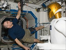 NASA astronaut Don Pettit, Expedition 30 flight engineer, enters data in a computer while working with Robonaut 2 humanoid robot in the Destiny laboratory of the International Space Station. (NASA)