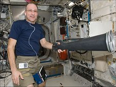 NASA astronaut Don Pettit, Expedition 30 flight engineer, holds a Microgravity Science Glovebox (MSG) glove in the Columbus laboratory of the International Space Station. (NASA)