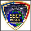 A three-sided patch with student's drawing of Earth edged in gear spokes underneath the space station. Words SSEP Mission 1 in foreground