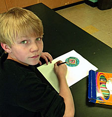 Fifth-grade boy drawing with colored pencils