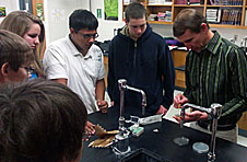 Students watch as an adult conducts a science experiment
