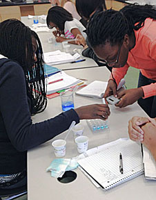 Students work with experiments at a table in a science laboratory