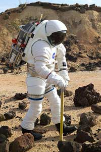 Engineer tries out a spacesuit in the rock yard