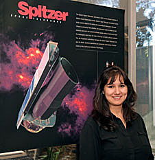 Farisa Morales stands next to a Spitzer Space Telescope poster
