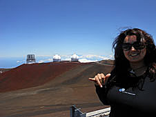 Farisa Morales atop a dormant volcano with large telescopes in the background
