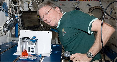 Astronaut Mike Fossum conducting the dry surface test as part of the Capillary Flow Experiments monitored from the ground on live video. (NASA)