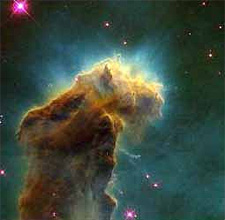 A brownish cloud of glowing gas in a star-filled area of space