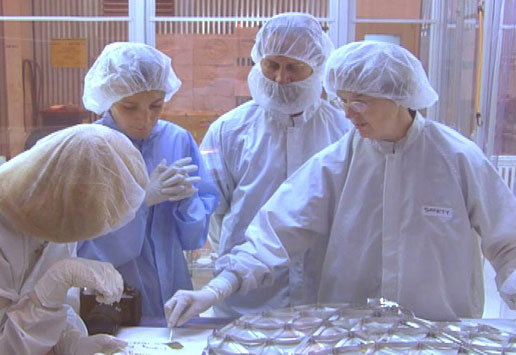 cleanroom team members look at Genesis samples