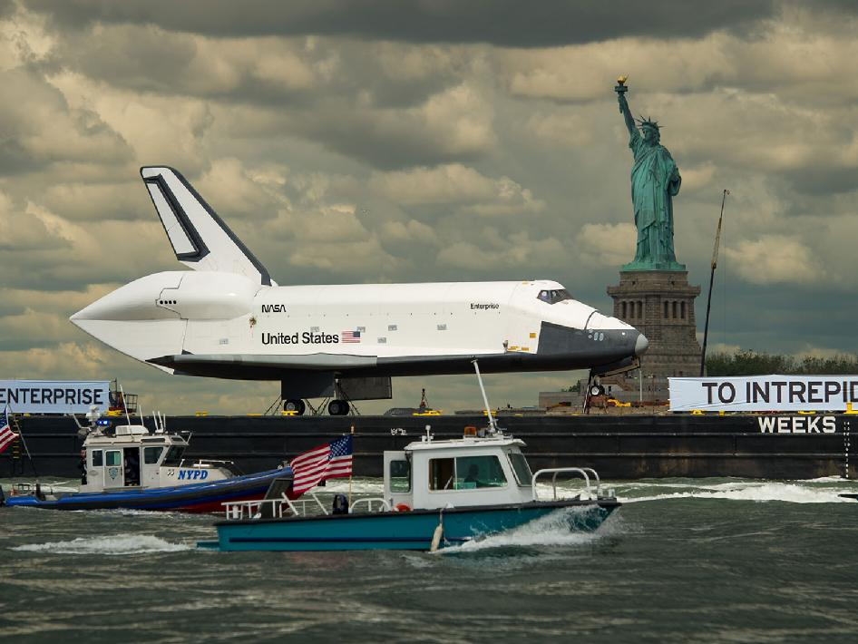 Enterprise sails on barge by the Statue of Liberty