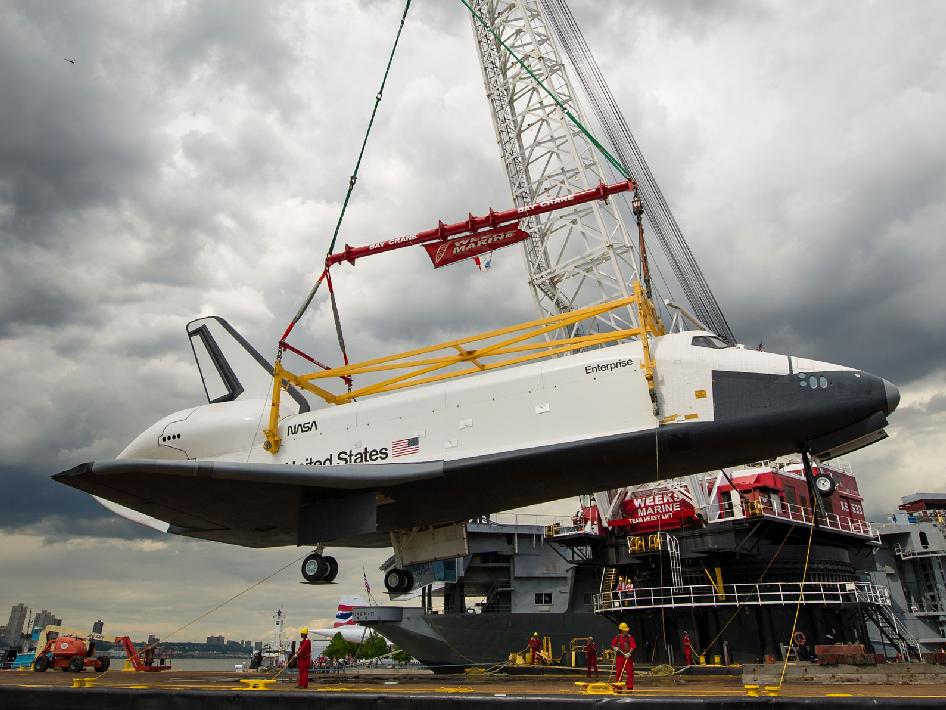A crane lifts Enterprise off barge.