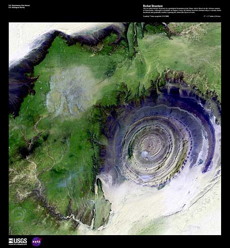 A green plateau wraps around a series of concentric tributaries on an eroded volcanic dome.