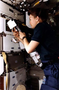 Astronaut Catherine G. Coleman, mission specialist, checks out an Astroculture sample on the mid-deck of the Earth-orbiting Space Shuttle Columbia during STS-73 in October 1995.