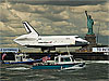 Space shuttle on barge in front of Statue of Liberty