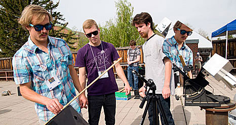 Three students set up equipment on an outdoor deck