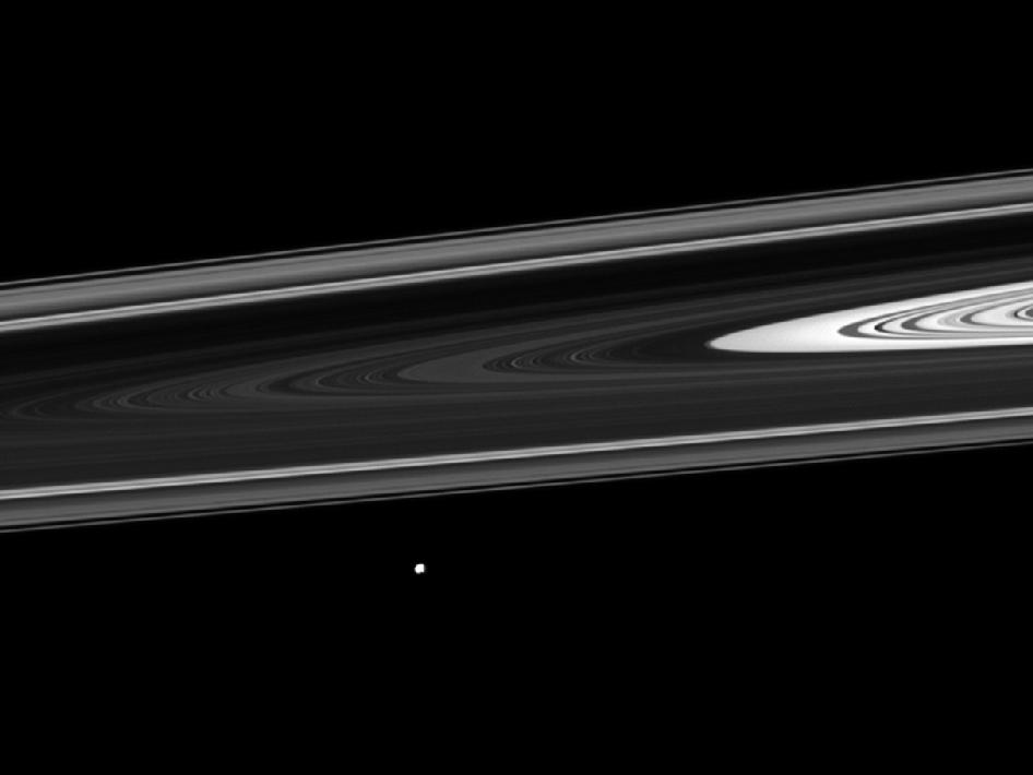 Saturn's small moon Epimetheus orbiting beyond the planet's rings.