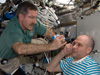 Expedition 30 Commander Dan Burbank, left, performs an intraocular pressure test on Flight Engineer Don Pettit