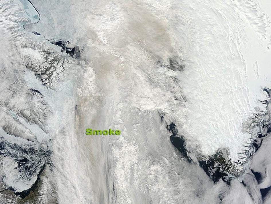 Smoke smears a dun stain across a swirl of white and whiter clouds cut with patches of aqua ice and navy sea