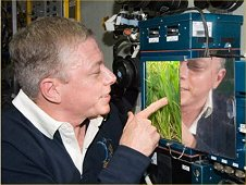 NASA astronaut Mike Fossum, Expedition 28 flight engineer, inspects a new growth experiment on the BIO-5 Rasteniya-2, or Plants-2, payload with its LADA-01 greenhouse in the Zvezda Service Module of the International Space Station. (NASA)