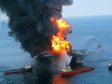 Platform supply vessels battle the blazing remnants of the off shore oil rig Deepwater Horizon. A Coast Guard MH-65C dolphin rescue helicopter and crew document the fire aboard the mobile offshore drilling unit Deepwater Horizon, while searching for survivors.