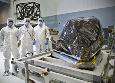 MIRI, wrapped in anti-static wrap, looks like an exotic moon rock near lab techs in bunny suits
