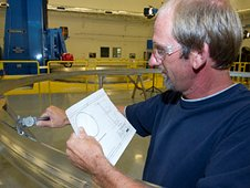 David Osborne, a machinist at the Marshall Center, takes measurements on a prototype aluminum ring.