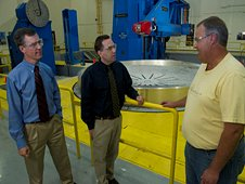 SLS team members discuss changes on an adapter ring designed and machined at the Marshall Center.