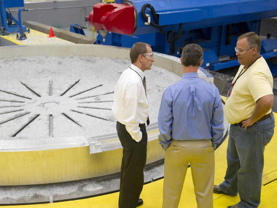 Three members of the Space Launch System team discuss the machining of an aluminum adapter at the Marshall Center.