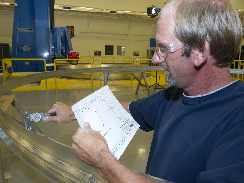 A machinist measures a prototype aluminum ring at the Marshall Center.