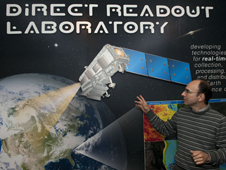 guy pointing to wall-sized poster of an artist's concept of NPP orbiting earth, with charts of data in the poster's foreground.