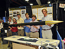 Vanderbilt students stand behind a table holding their rocket with the payload