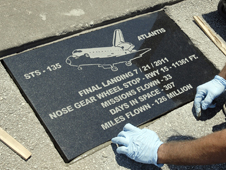 Artist Chad Stout installs a commemorative granite paver at the Shuttle Landing Facility
